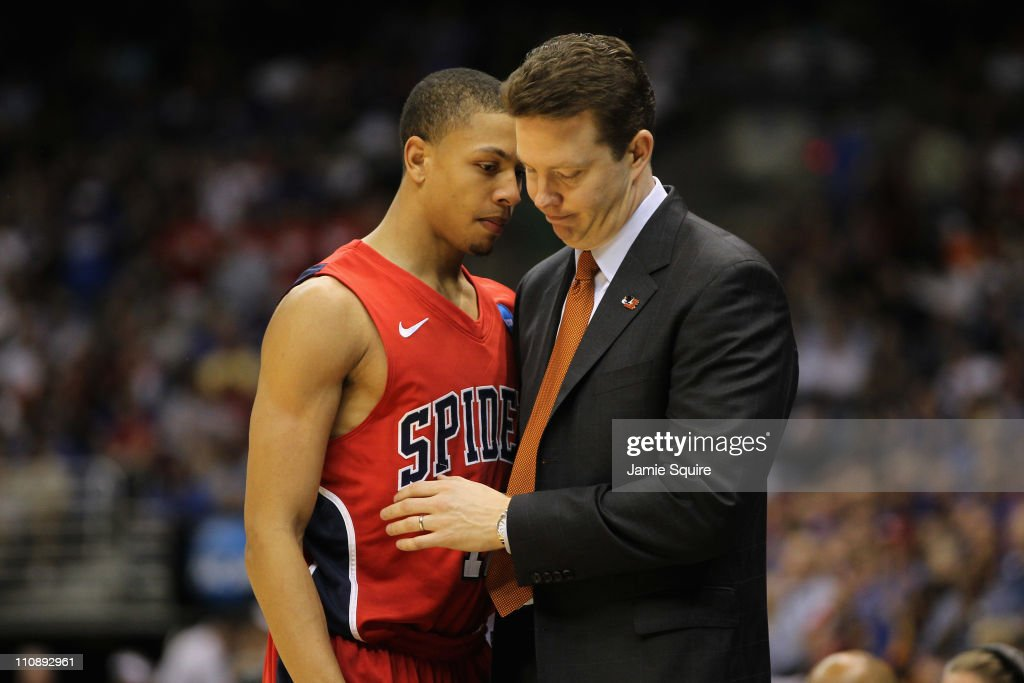 Head coach Chris Mooney of the Richmond Spiders comforts Kevin Smith #12 after the southwest regional of the 2011 NCAA men's basketball tournament at the Alamodome on March 25, 2011 in San Antonio, Texas. Kansas defeated Richmond 77-57.