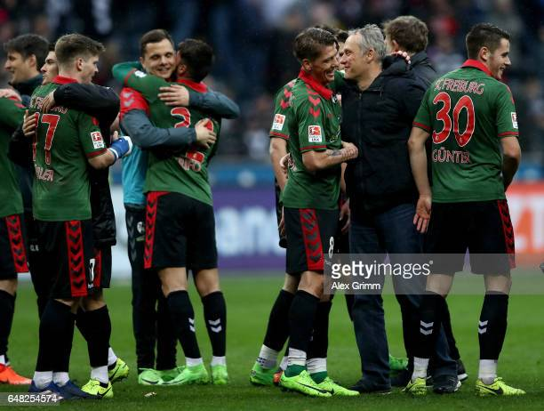 Head coach Christian Streich celebrates with his players after winning the Bundesliga match between Eintracht Frankfurt and SC Freiburg at...