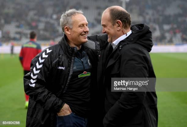 Head coach Christian Streich of Freiburg hughs manager Joerg Schmadtke of Koeln during the Bundesliga match between SC Freiburg and 1 FC Koeln at...