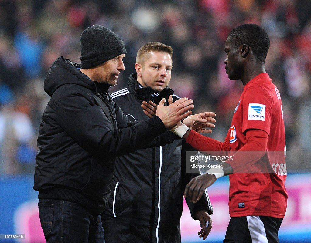 Head coach Christian Streich of Freiburg (L) speaks to during change of Fallou Diagne during the Bundesliga match between SC Freiburg and Eintracht Frankfurt at MAGE SOLAR Stadium on February 22, 2013 in Freiburg, Germany.