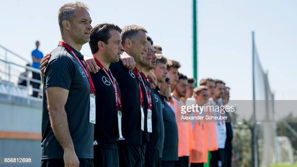 Head coach Christian Wueck of Germany and the assistant team of Germany sing the national anthem during the UEFA U17 elite round match between...
