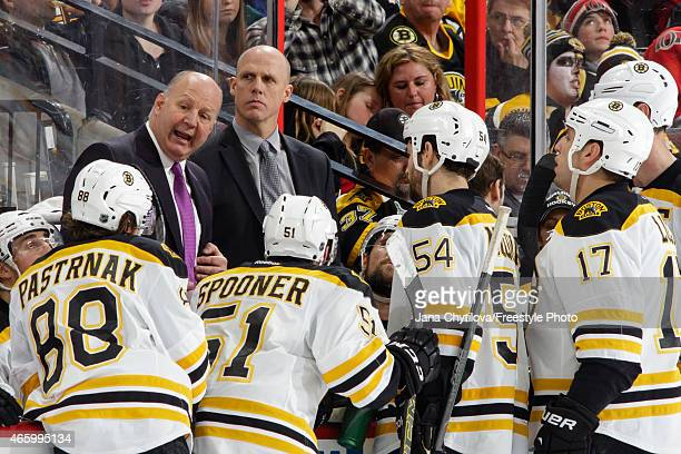 Head coach Claude Julien and assistant coach Doug Houda of the Boston Bruins talk to their players during a timeout against the Ottawa Senators at...