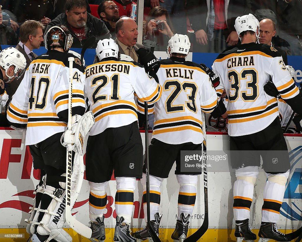 Head Coach Claude Julien of the Boston Bruins calls a time out and gathers Tuukka Rask #40, Loui Eriksson #21, Chris Kelly #23 and Zdeno Chara #33 around the bench after going down 4-0 in the 2nd period during an NHL game against the Detroit Red Wings at Joe Louis Arena on November 27, 2013 in Detroit, Michigan.
