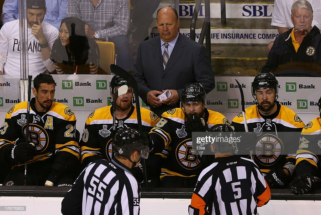 Head coach Claude Julien of the Boston Bruins looks on with his team as linesman Shane Heyer #55 and referee Chris Rooney #5 approach in Game Three of the 2013 NHL Stanley Cup Final against the Chicago Blackhawks at TD Garden on June 17, 2013 in Boston, Massachusetts.