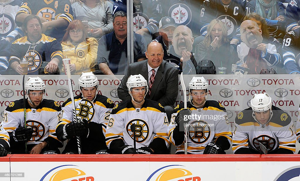 Head Coach Claude Julien of the Boston Bruins smiles as fans hold cardboard cutouts of his head behind the bench during second period action against the Winnipeg Jets on December 19, 2014 at the MTS Centre in Winnipeg, Manitoba, Canada.
