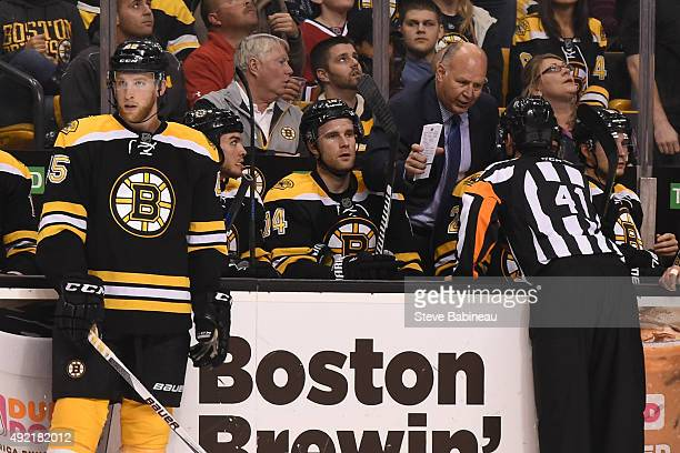 Head Coach Claude Julien of the Boston Bruins talks with referee Mark Lemelin during a time out against the Montreal Canadiens at the TD Garden on...