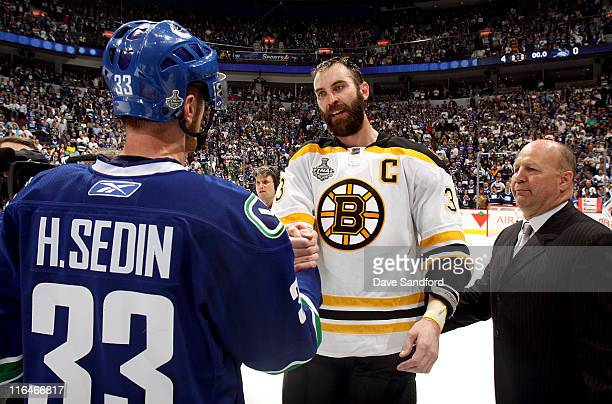 Head coach Claude Julien of the Boston Bruins waits as Zdeno Chara shakes hands Henrik Sedin of the Vancouver Canucks after the Bruins defeated the...