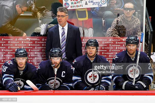 Head Coach Claude Noel Bryan Little Andrew Ladd John Albert and Blake Wheeler of the Winnipeg Jets look on from the bench during second period action...