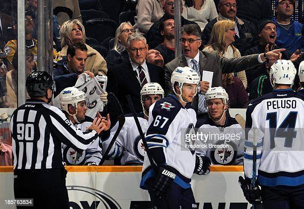 Head coach Claude Noel of the Winnipeg Jets has a discussion with linesman Andy McElman during a game against the Nashville Predators at Bridgestone...