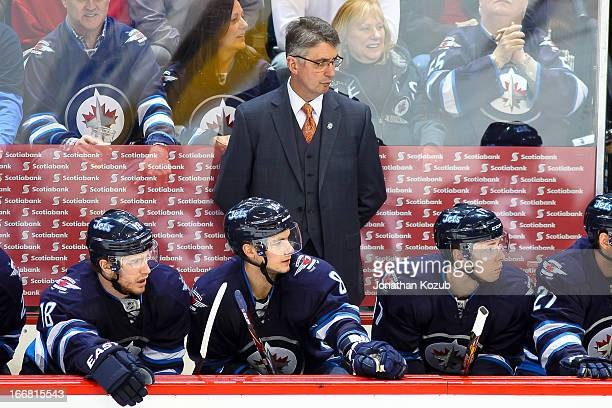 Head Coach Claude Noel of the Winnipeg Jets looks on from the bench behind players Bryan Little Alexander Burmistrov and James Wright during the...