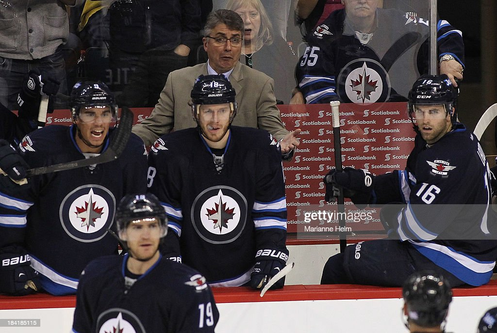 Head coach Claude Noel of the Winnipeg Jets talks to an official from the bench in the third period action of an NHL game at the MTS Centre on October 11, 2013 in Winnipeg, Manitoba, Canada.