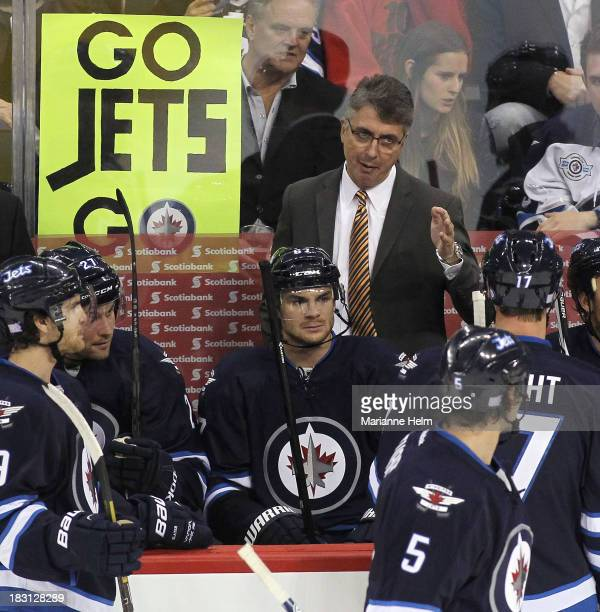 Head coach Claude Noel of the Winnipeg Jets talks to his team on the bench in third period action during an NHL home opener game against the Los...