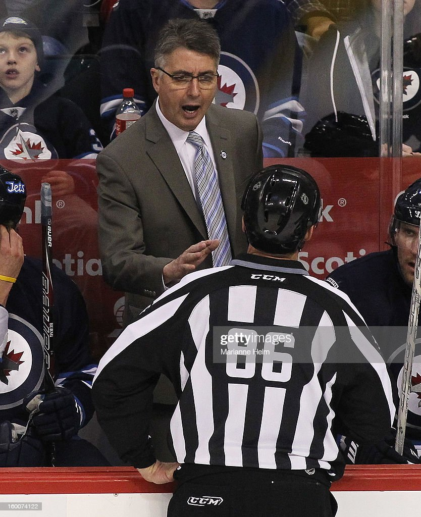 Head coach Claude Noel of the Winnipeg Jets talks to linesman Brad Lawarowich from the bench in third-period action during a game against the Pittsburgh Penguins on January 25, 2013 at the MTS Centre in Winnipeg, Manitoba, Canada.