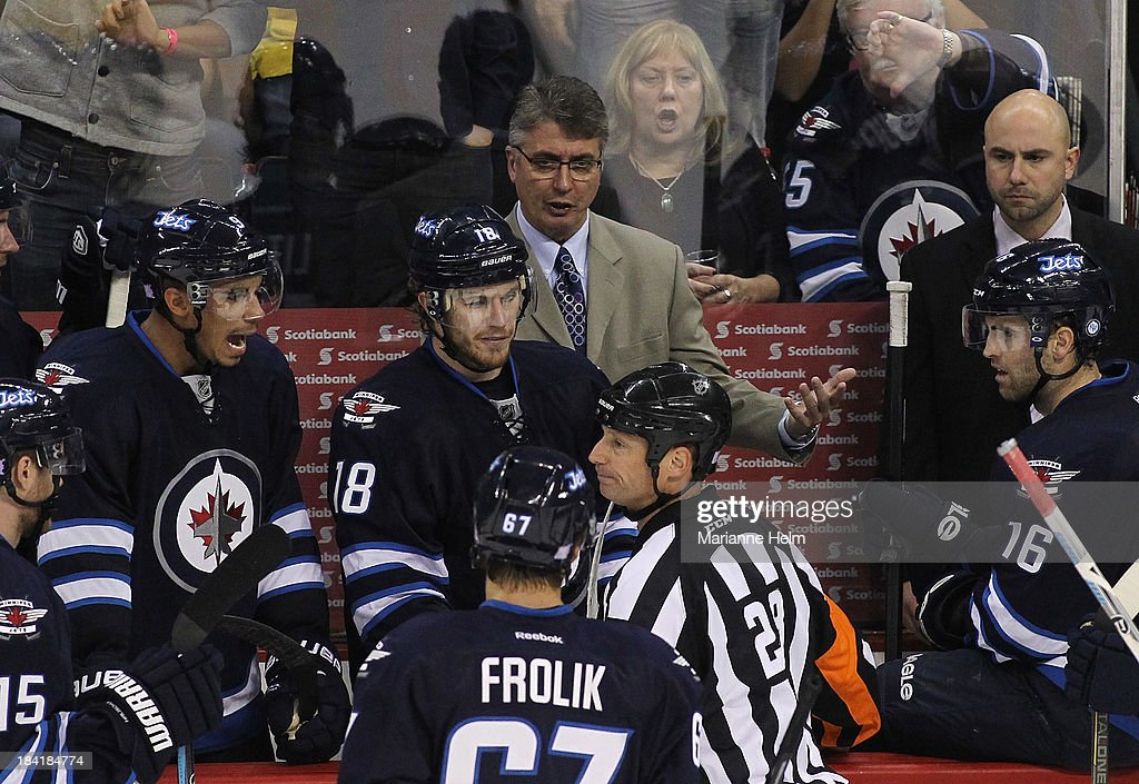 Head coach Claude Noel of the Winnipeg Jets talks to referee Chris Lee #28 from the bench in third period action of an NHL game at the MTS Centre on October 11, 2013 in Winnipeg, Manitoba, Canada.
