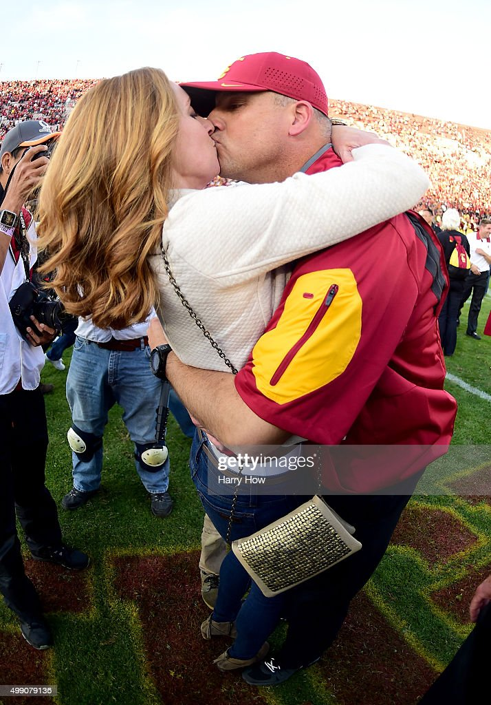 Head coach Clay Helton of the USC Trojans and his wife Angela kiss after a 40-21 win over the UCLA Bruins at Los Angeles Memorial Coliseum on November 28, 2015 in Los Angeles, California.