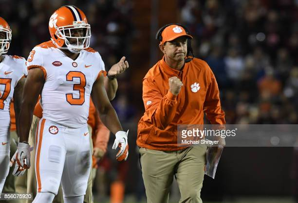Head coach Dabo Swinney of the Clemson Tigers celebrates on the sideline after a touchdown against the Virginia Tech Hokies at Lane Stadium on...