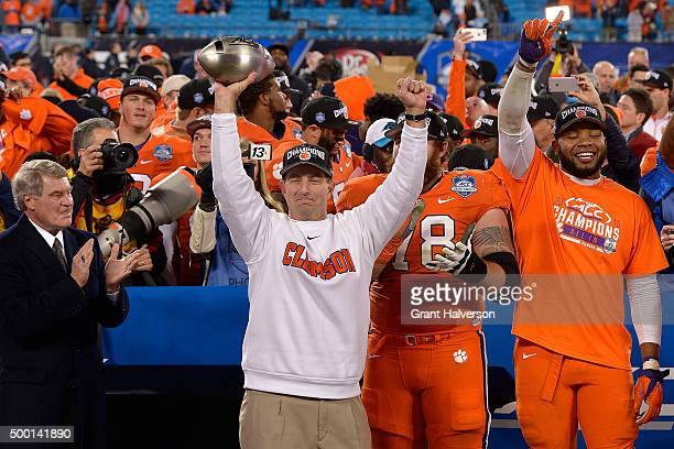 Head coach Dabo Swinney of the Clemson Tigers celebrates with the trophy after a win against the North Carolina Tar Heels during the Atlantic Coast...