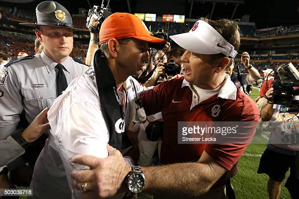 Head coach Dabo Swinney of the Clemson Tigers greets head coach Bob Stoops of the Oklahoma Sooners after the Clemson Tigers defeat the Oklahoma...
