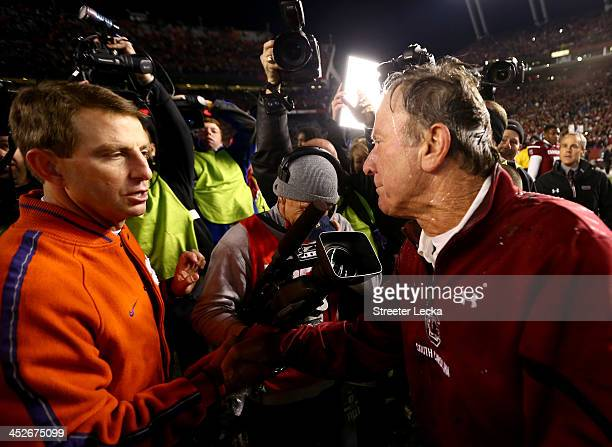 Head coach Dabo Swinney of the Clemson Tigers shakes hands with head coach Steve Spurrier of the South Carolina Gamecocks after a 3117 win for the...