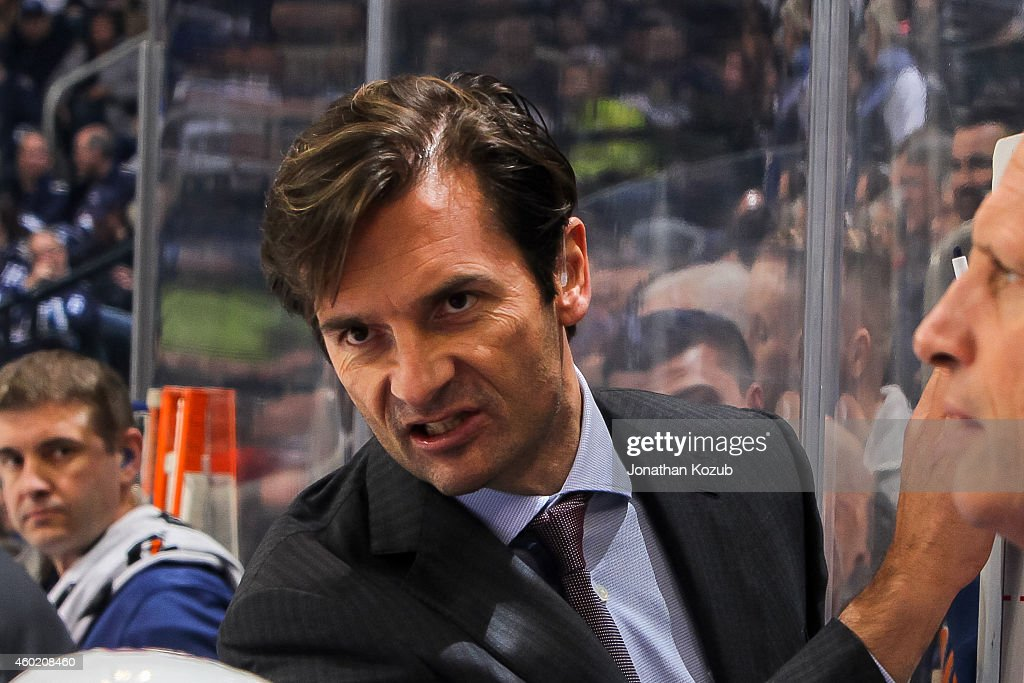 Head Coach <a gi-track='captionPersonalityLinkClicked' href=/galleries/search?phrase=Dallas+Eakins&family=editorial&specificpeople=714367 ng-click='$event.stopPropagation()'>Dallas Eakins</a> of the Edmonton Oilers discusses strategy with players at the bench during a third period timeout against the Winnipeg Jets on December 3, 2014 at the MTS Centre in Winnipeg, Manitoba, Canada. The Jets defeated the Oilers 3-2 in overtime.