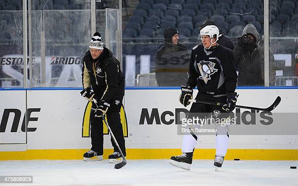 Head Coach Dan Bylsma of the Pittsburgh Penguins looks to pass the puck as Sidney Crosby of the Pittsburgh Penguins looks on during the 2014 NHL...