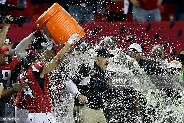 Head coach Dan Quinn of the Atlanta Falcons has gatorade dumped on him by his team late in the game against the Green Bay Packers in the NFC...