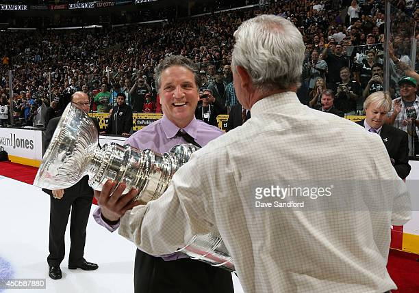 Head coach Darryl Sutter of the Los Angeles Kings hands off the Stanley Cup to Kings general manager Dean Lombardi after his team won Game Five 32 in...