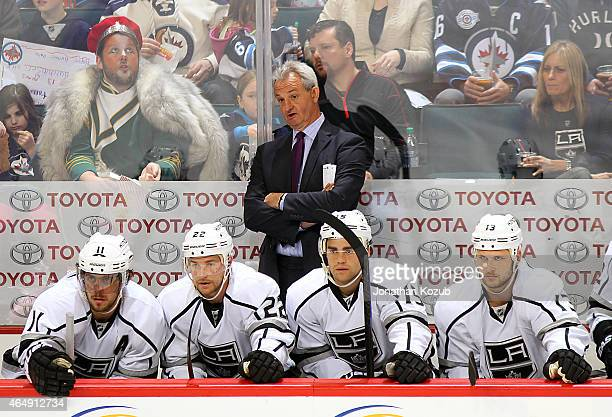 Head Coach Darryl Sutter of the Los Angeles Kings watches the play from the bench behind players Anze Kopitar Trevor Lewis Andy Andreoff and Kyle...