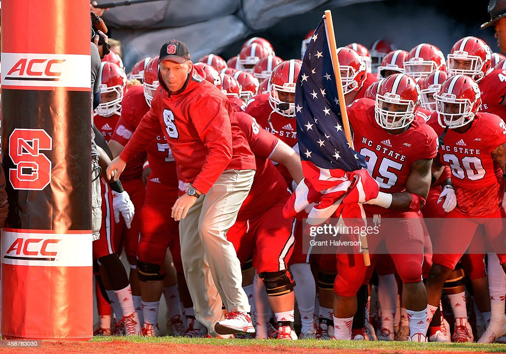 Head coach <a gi-track='captionPersonalityLinkClicked' href=/galleries/search?phrase=Dave+Doeren&family=editorial&specificpeople=3913248 ng-click='$event.stopPropagation()'>Dave Doeren</a> and the North Carolina State Wolfpack prepare to take the field for a game against the Georgia Tech Yellow Jackets at Carter-Finley Stadium on November 8, 2014 in Raleigh, North Carolina.
