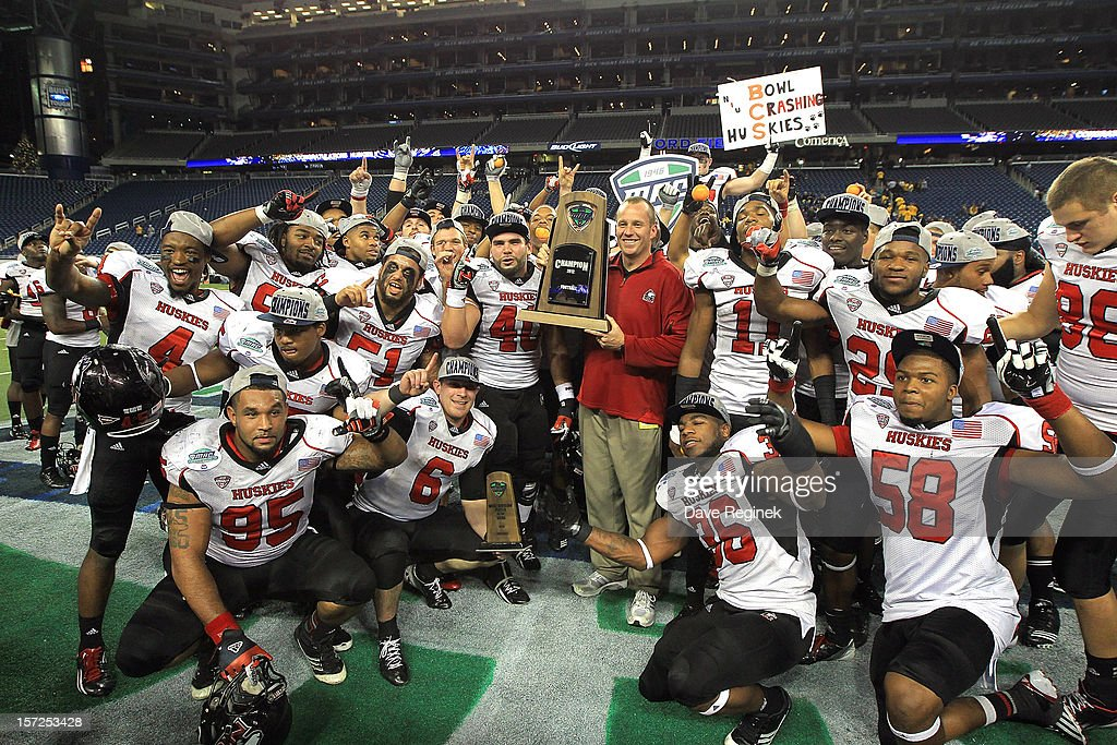 Head coach Dave Doeren of the Northern Illinois Huskies is surrounded by his team as he holds the championship trophy after defeating the Kent State Golden Flashes 44-37 during the Mid-American Conference Championship game at Ford Field on November 30, 2012 in Detroit, Michigan.