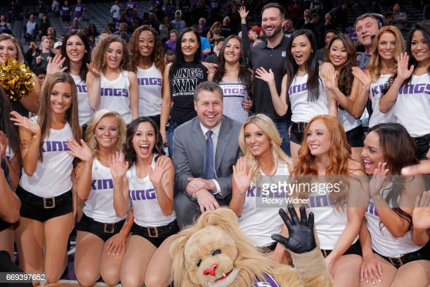 Head coach Dave Joerger of the Sacramento Kings and emcee Scott Freshour pose for a photo with the Sacramento Kings dance team after the game against...