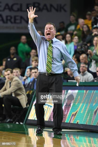 Head coach Dave Paulsen of the George Mason Patriots signals a play during a college basketball tournament against the Cal State Northridge Matadors...