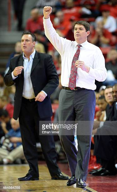 Head coach Dave Rice of the UNLV Rebels gestures to his players as associate head coach Heath Schroyer looks on during their game against the Utah...