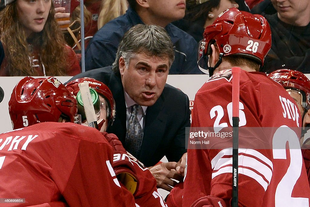 Head coach Dave Tippett of the Arizona Coyotes instructs players Connor Murphy and Michael Stone during a third period timeout against the...