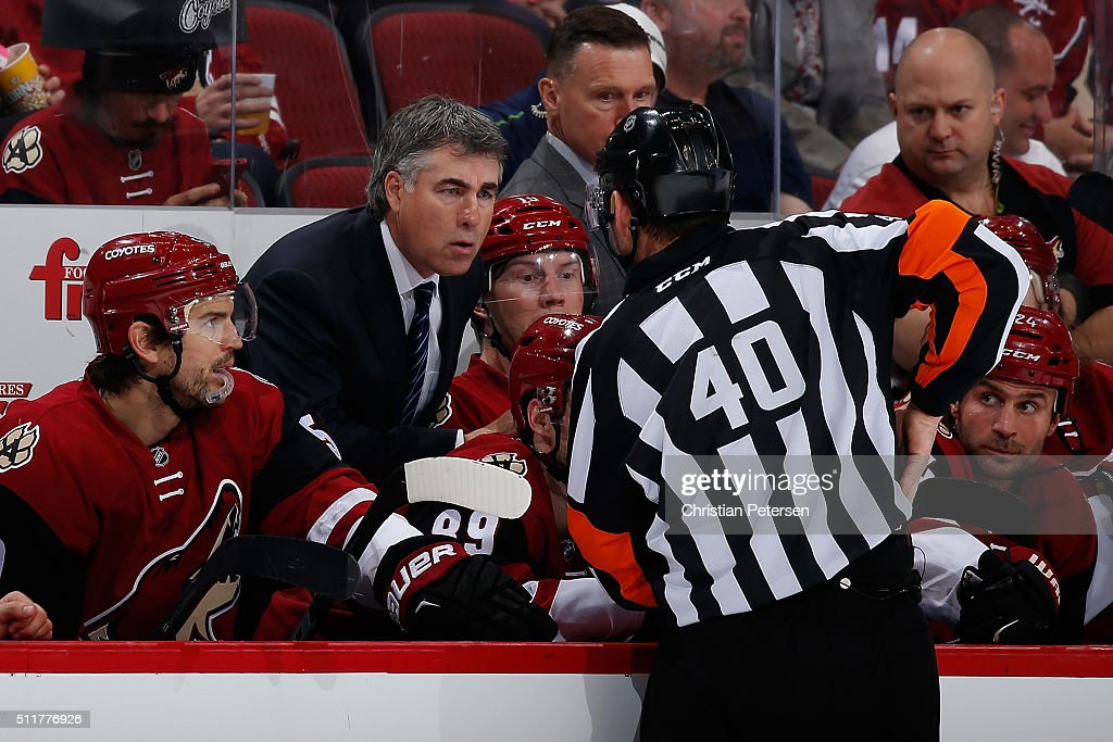 Head coach Dave Tippett of the Arizona Coyotes talks with referee Steve Kozari during the NHL game against the Dallas Stars at Gila River Arena on...