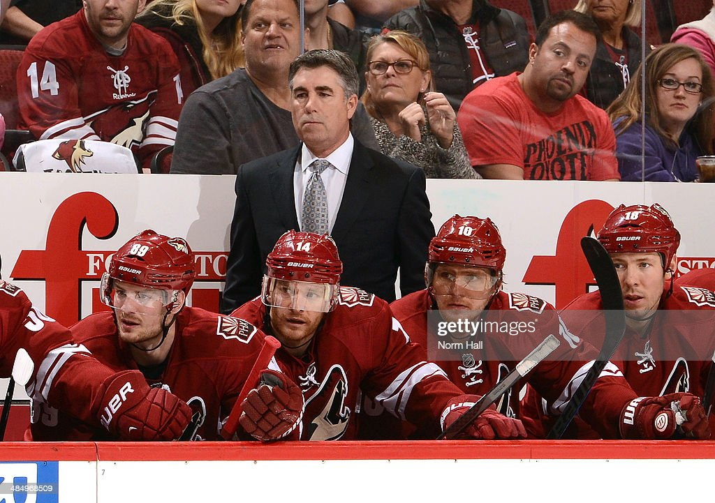 Head Coach Dave Tippett of the Phoenix Coyotes watches play from behind the bench against the Dallas Stars at Jobingcom Arena on April 13 2014 in...
