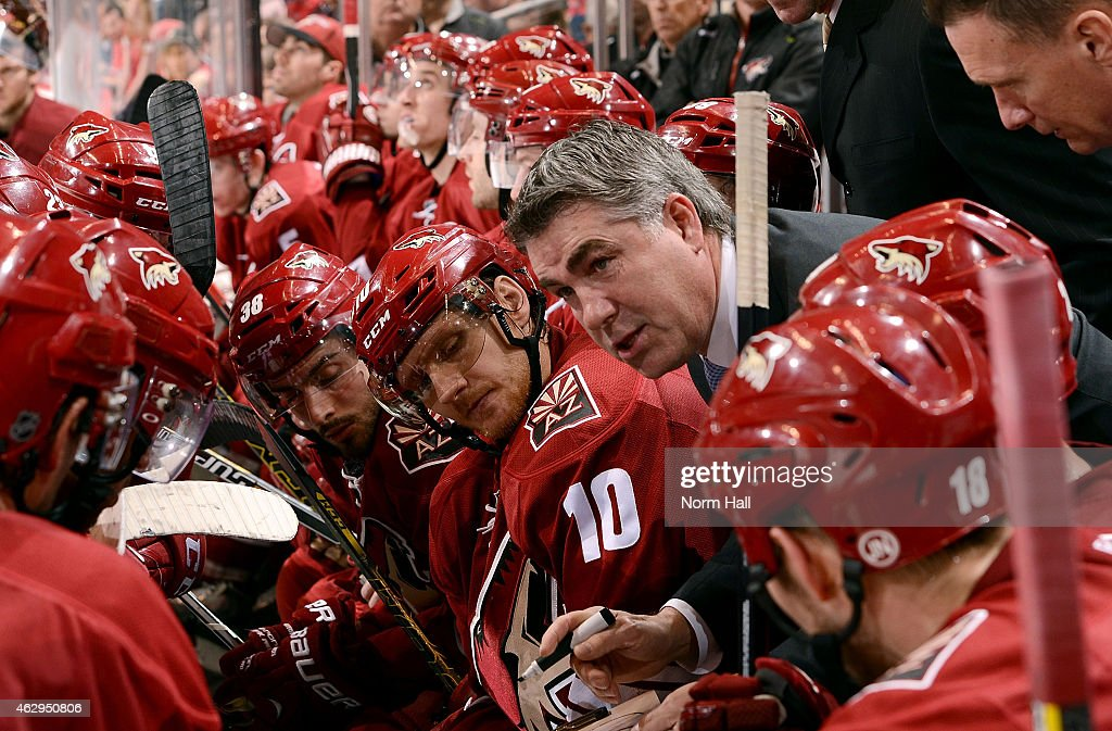Head coach Dave Tippett talks with players during a third period timeout against the Detroit Red Wings at Gila River Arena on February 7 2015 in...