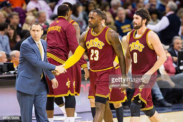 Head coach David Blatt celebrates with LeBron James and Kevin Love of the Cleveland Cavaliers during the first half against the Miami Heat at Quicken...
