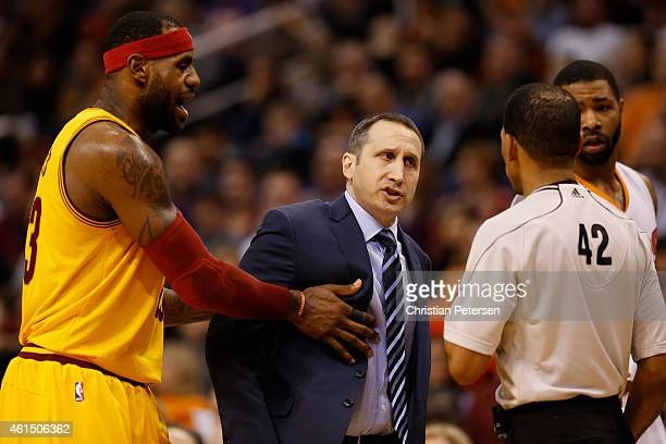 Head coach David Blatt of the Cleveland Cavaliers reacts to referee Eric Lewis as LeBron James holds him back during the second half of the NBA game...