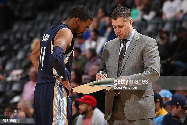 Head coach David Joerger of the Memphis Grizzlies talks with Mike Conley of the Memphis Grizzlies against the Denver Nuggets at Pepsi Center on...