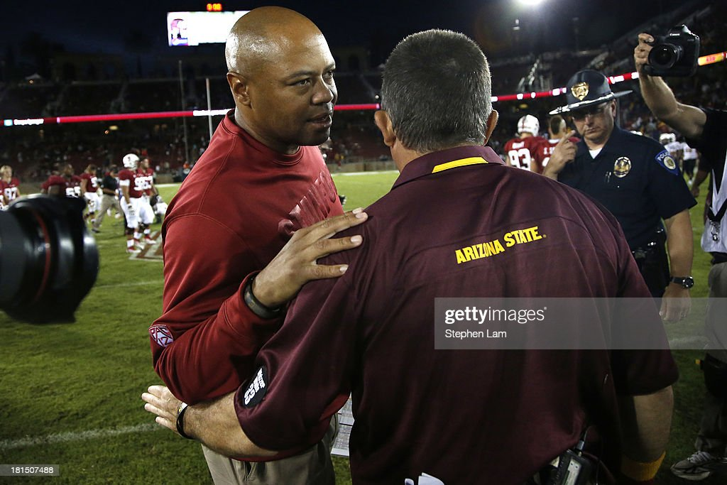 Head coach David Shaw (L) of the Stanford Cardinal speaks with head coach Todd Graham of the Arizona State Sun Devils after their game at Stanford Stadium on September 21, 2013 in Stanford, California. The Cardinals defeated the Sun Devils 42-28.