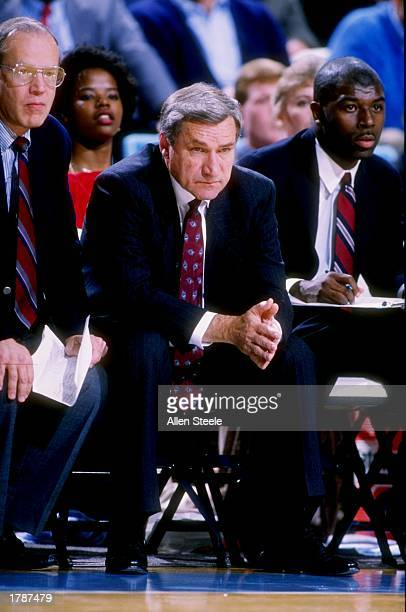Head coach Dean Smith center sits with assistant coaches Bill Guthridge left and Phil Ford right on the bench during a North Carolina Tar Heels game...