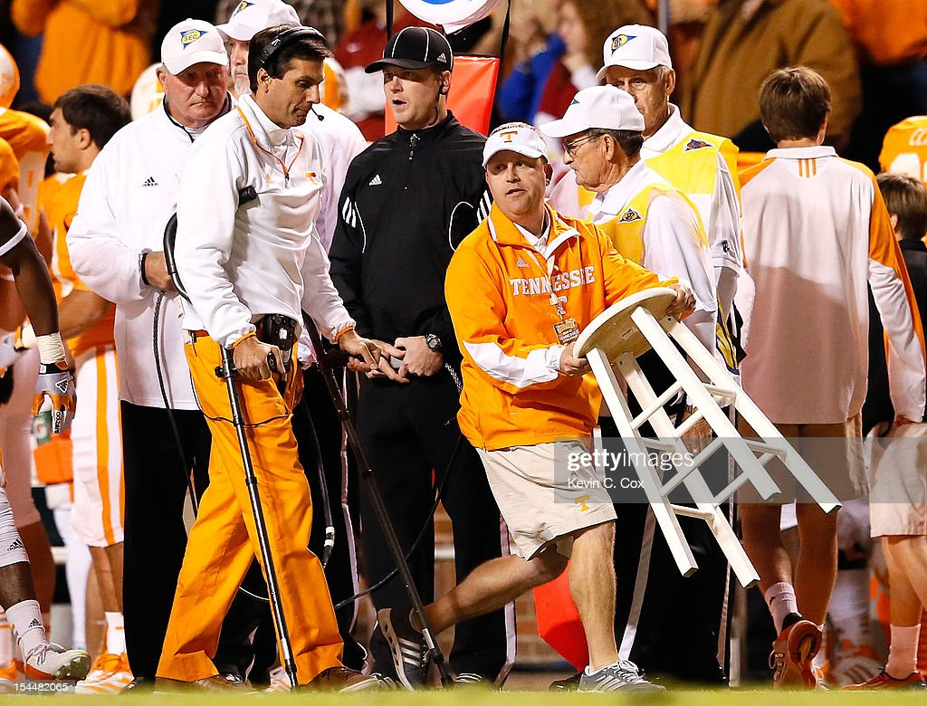 Head coach Derek Dooley of the Tennessee Volunteers uses crutches to walk to a stool carried on the sideline for him to sit on during the game against the Alabama Crimson Tide at Neyland Stadium on October 20, 2012 in Knoxville, Tennessee.