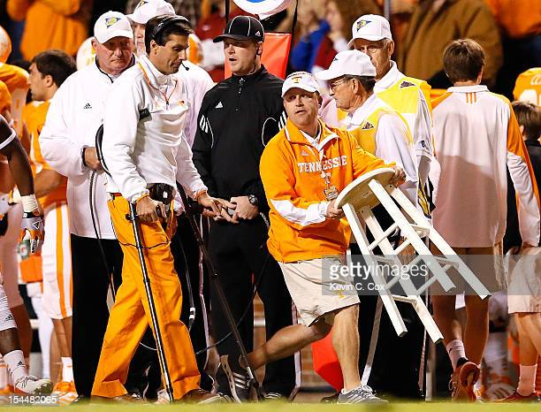 Head coach Derek Dooley of the Tennessee Volunteers uses crutches to walk to a stool carried on the sideline for him to sit on during the game...