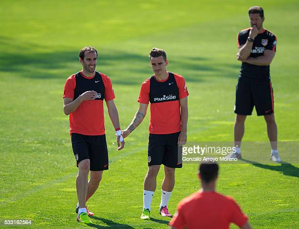 Head coach Diego Pablo Simeone supervises Atletico de Madrid players Diego Godin and Antoine Griezmann during the training session during the Club...