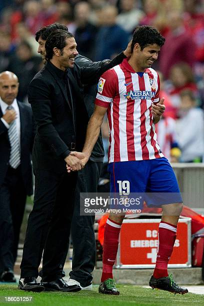 Head coach Diego Simeone of Atletico de Madrid congratulates goalscorer Diego Costa during the La Liga match between Club Atletico de Madrid and Real...