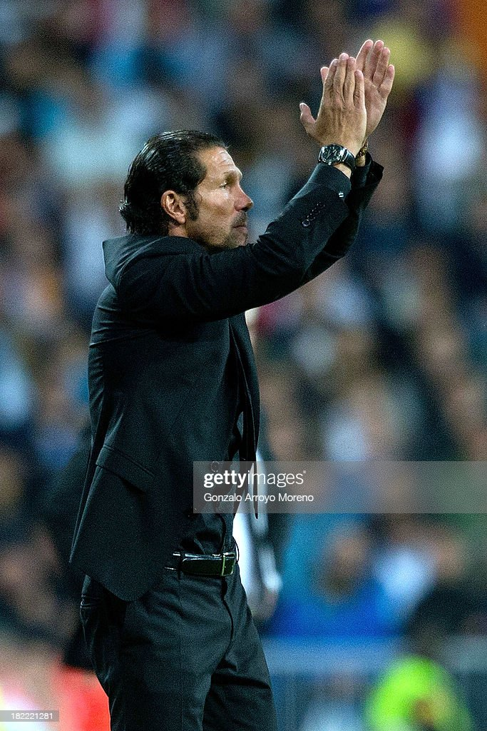 Head coach Diego Simeone of Atletico de Madrid congratulates their players during the La Liga match between Real Madrid CF and Club Atletico de Madrid at Estadio Santiago Bernabeu on September 28, 2013 in Madrid, Spain.