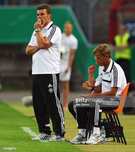 Head coach Dieter Hecking and assistant coach Andries Jonker of Wolfsburg look on during the DFB Cup first round match between Karlsruher SC and VfL...