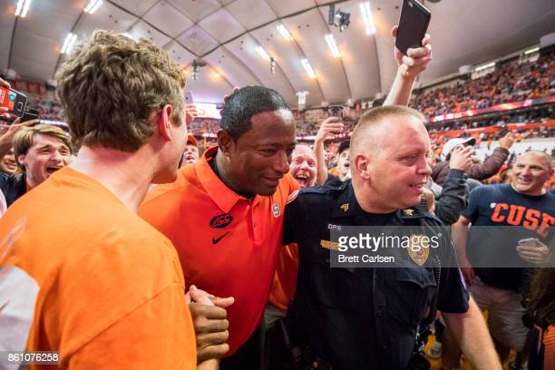 Head coach Dino Babers of the Syracuse Orange is escorted off the field by police after fans stormed the field following an upset victory against the...