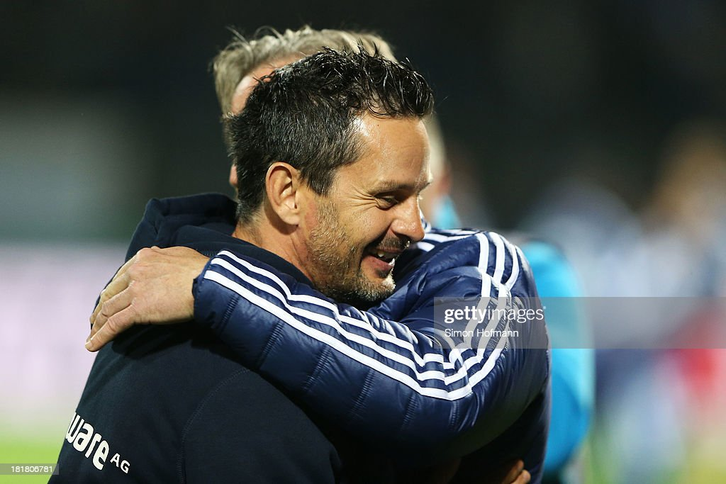 Head coach Dirk Schuster of Darmstadt hugs head coach <a gi-track='captionPersonalityLinkClicked' href=/galleries/search?phrase=Jens+Keller&family=editorial&specificpeople=2382918 ng-click='$event.stopPropagation()'>Jens Keller</a> of Schalke during the DFB Cup second round match between Darmstadt 98 and Schalke 04 at Stadion am Boellenfalltor on September 25, 2013 in Darmstadt, Germany.